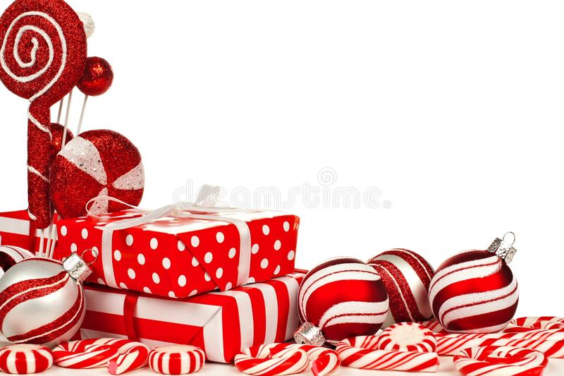 Red and white Christmas corner border with gifts, baubles, candy. Red and white Christmas corner border with gifts, baubles and candy against a white background royalty free stock photography