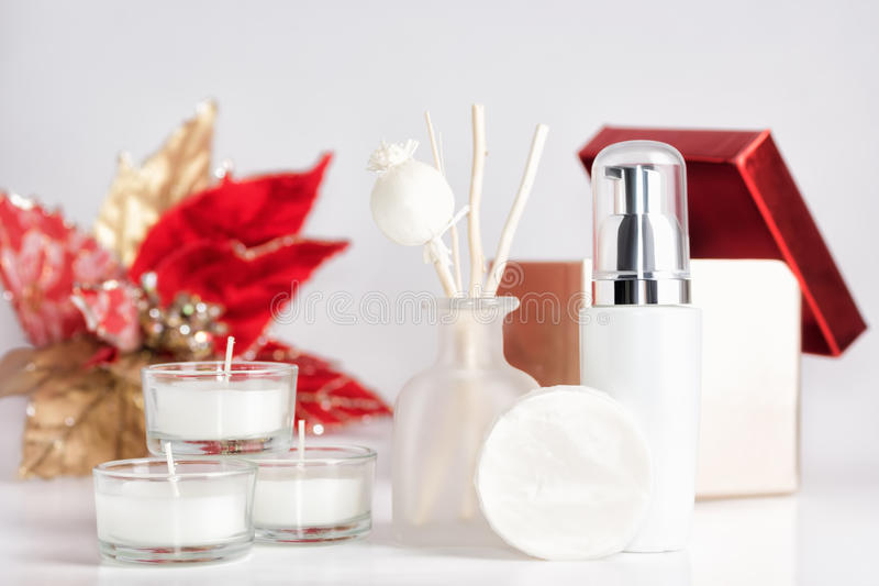 Red and white christmas spa cosmetics background. Aroma sticks, candles, soap and serum on table. Gift box and flower in background. Body care, skin treatment stock images