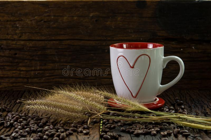 Red and white coffee cup with heart shape pattern, dry grass flowers and coffee beans on wood table stock image