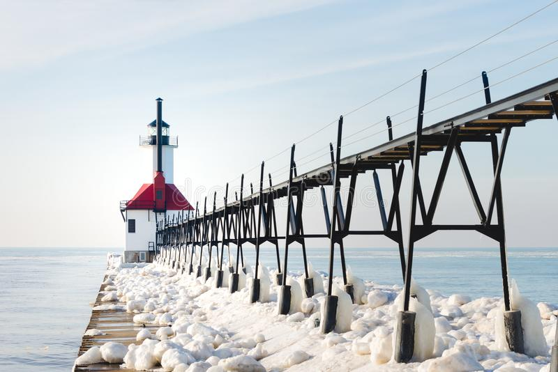 Red and White Concrete Lighthouse Surrounded by Snow Near Body of Water royalty free stock photos