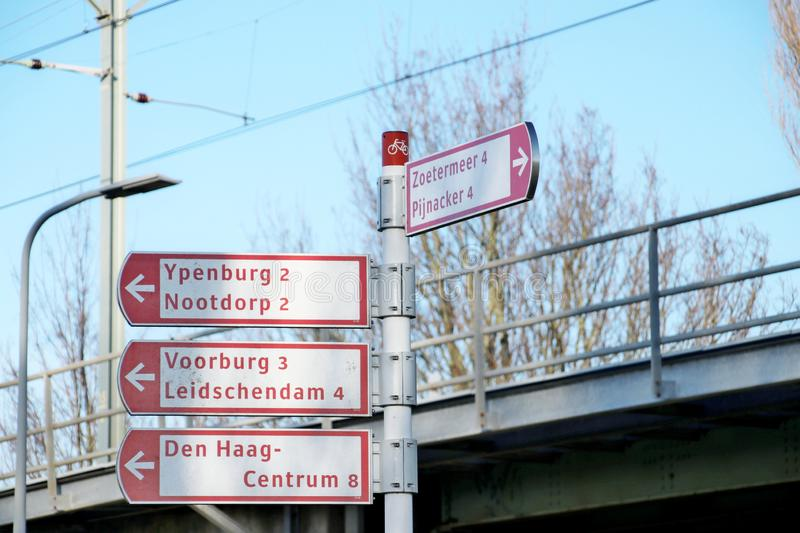 Red and white direction signs for several districts in The Hague for Cyclists in the Netherlands. Red and white direction signs for several districts in The royalty free stock photos