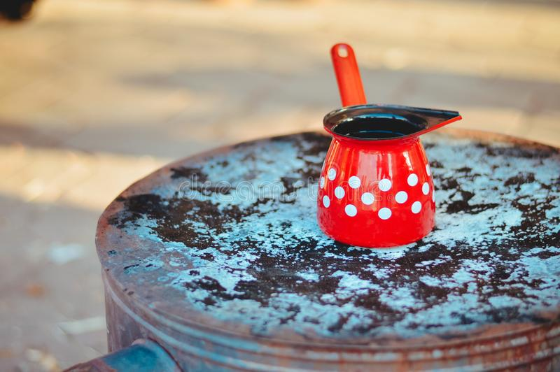 Red, white dot turkish coffee pot on top of old stove royalty free stock photo