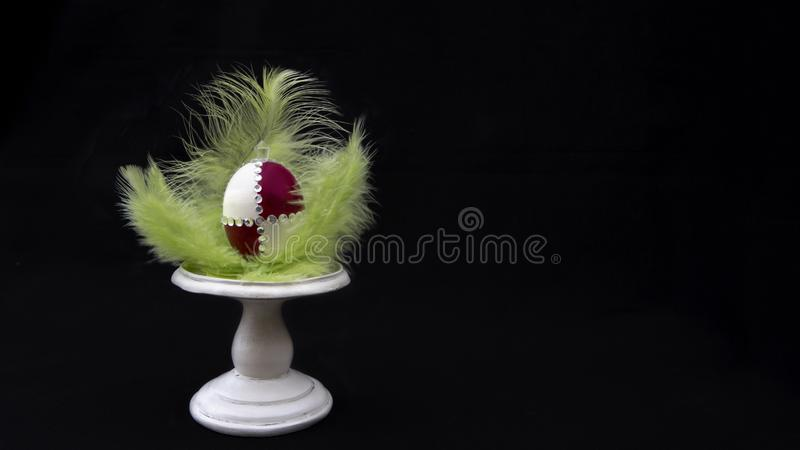Red and white ester egg with green feathers royalty free stock photography
