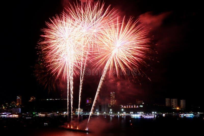Red and white fireworks splashing in the night sky over Pattaya bay, Pattaya city, Thailand stock photos