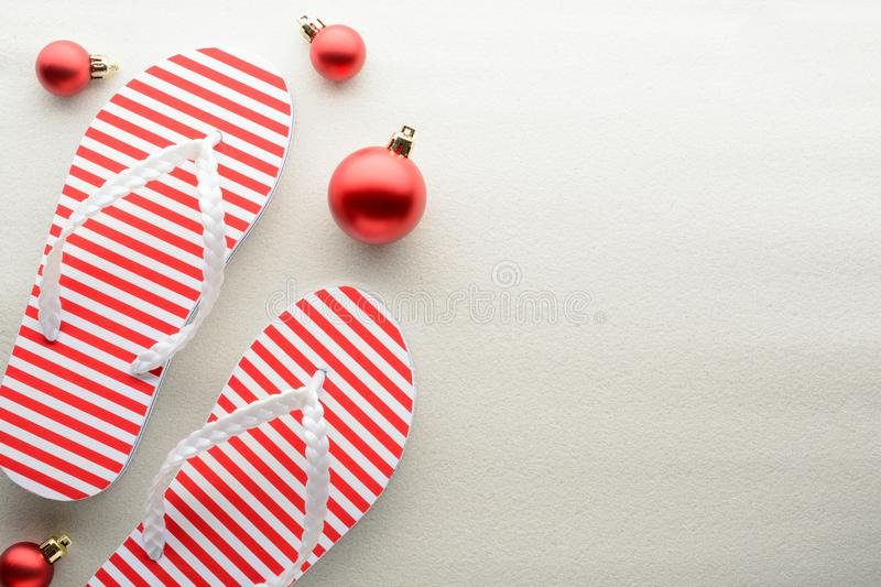 Red and white flip flops and Christmas ornaments stock photography