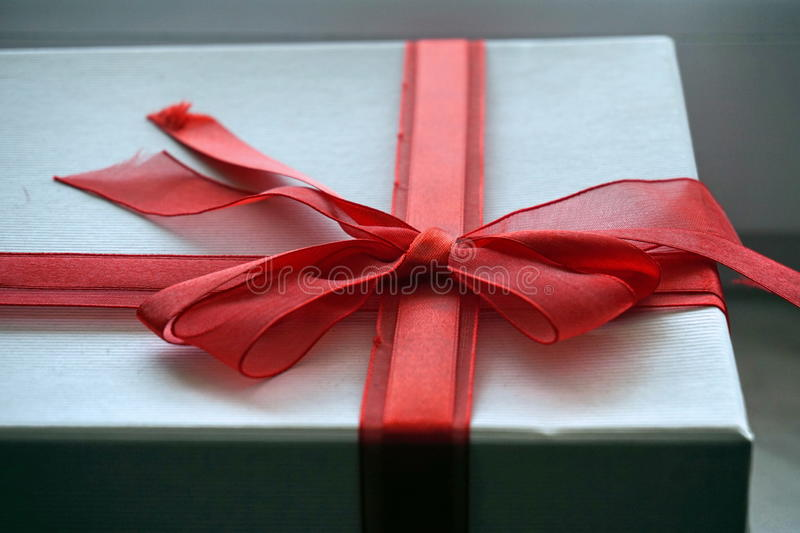 Red and white gift box with a ribbon on the top in a shape of great topknot. Red and white gift box with a scarlet ribbon on the top in a shape of great topknot stock photos