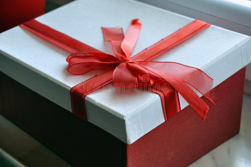 Red and white gift box with a ribbon on the top in a shape of great topknot. Red and white gift box with a scarlet ribbon on the top in a shape of great topknot stock photography