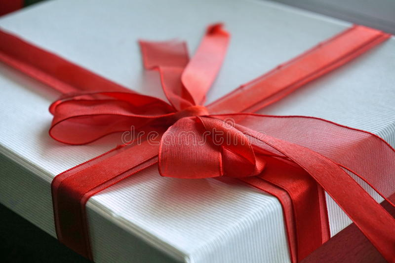 Red and white gift box with a ribbon on the top in a shape of great topknot. Red and white gift box with a scarlet ribbon on the top in a shape of great topknot stock photo