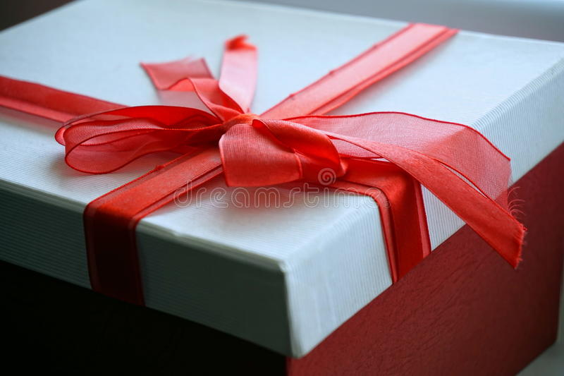 Red and white gift box with a ribbon on the top in a shape of great topknot. Red and white gift box with a scarlet ribbon on the top in a shape of great topknot royalty free stock photo