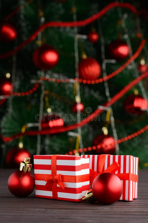 Red-white gift boxes on background of decorated Christmas tree stock images