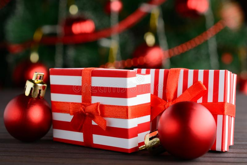 Red-white gift boxes on background of decorated Christmas tree stock photos
