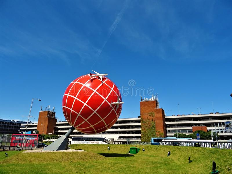 Red and White Globe Statue Near Brown and White Concrete Building stock image