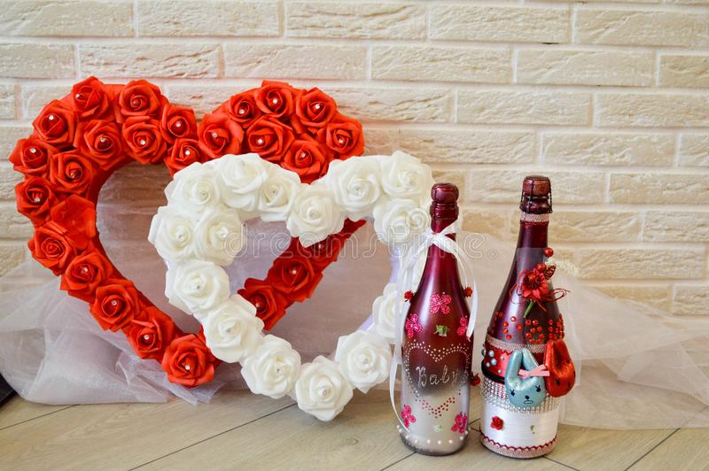 Red and white heart with roses. Two homemade bottles of champagne. Against the background of a brick wall. stock images