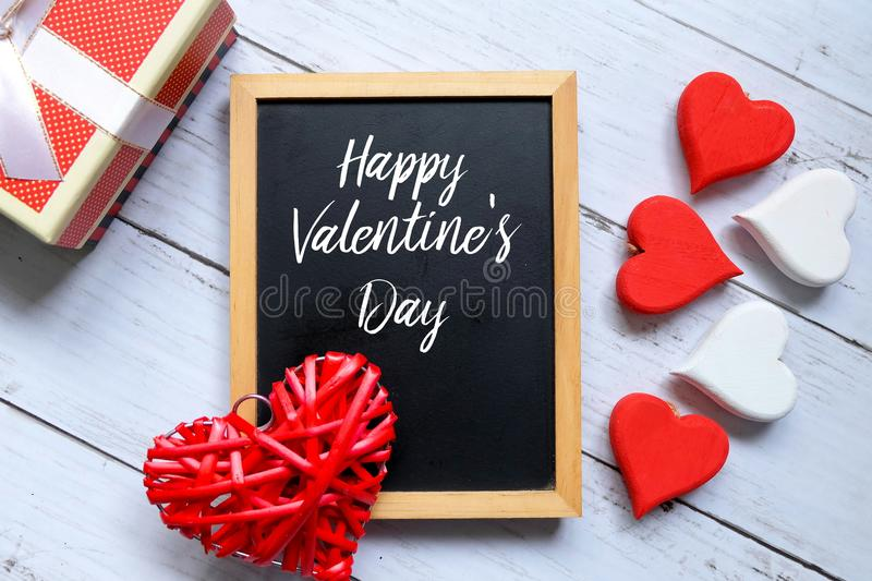 Red and white heart wooden handcraft and box white a blackboard written with Happy Valentine`s day. stock image
