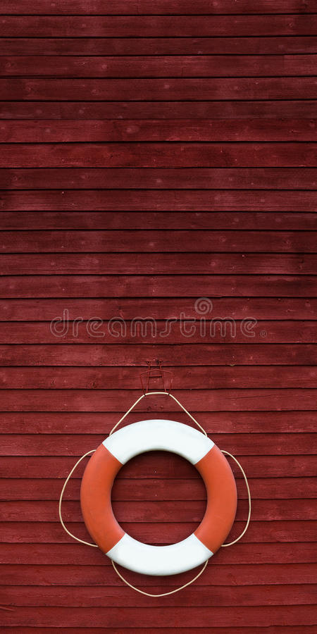 Red and white life buoy on the side of a wooden ship. Red and white life buoy hanging on the side of a wooden ship stock images