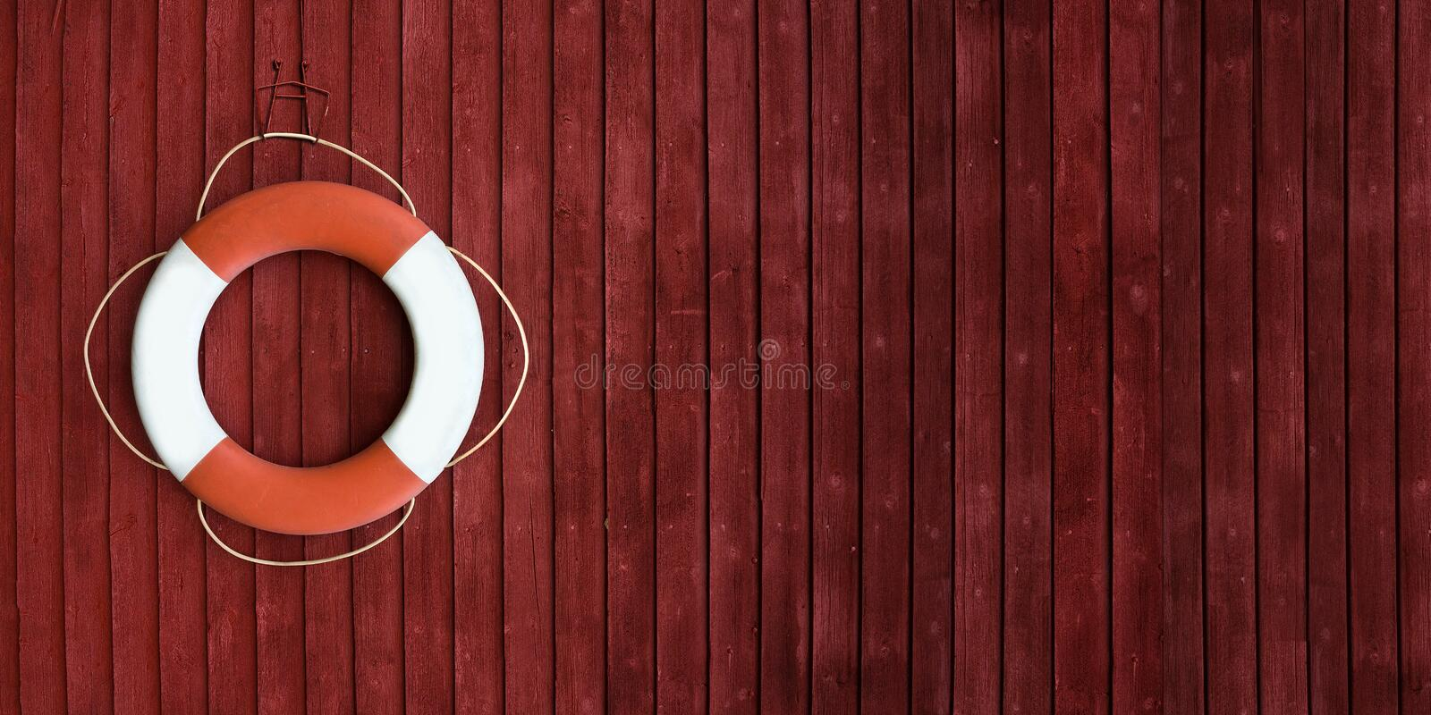 Red and white life buoy on the side of a wooden ship. Red and white life buoy hanging on the side of a wooden ship royalty free stock images