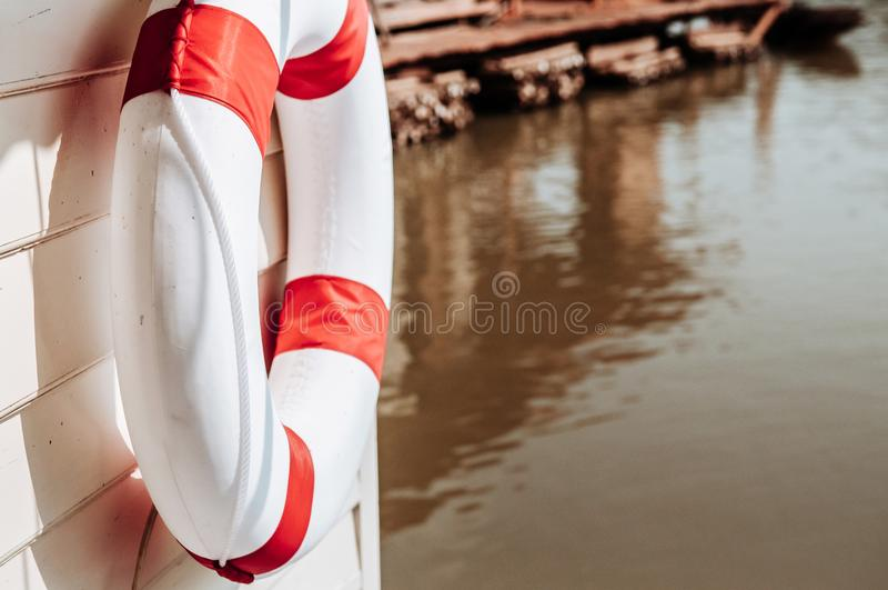 Red and white life buoy torus hanging on wooden wall of river fl. Close up shot of Red and white life buoy torus hanging on white wooden wall of river floating stock images