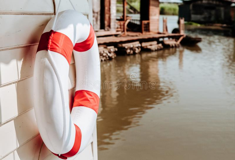 Red and white life buoy torus hanging on wooden wall of river fl. Red and white life buoy torus hanging on white wooden wall of river floating house or raft royalty free stock photo