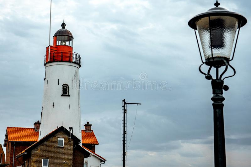 Red and white lighthouse with onosch on the seaport of the Netherlands in cloudy weather. Red and white lighthouse close-up with small windows royalty free stock photography
