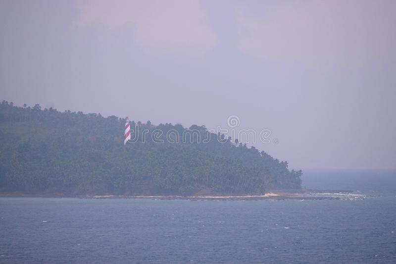 Red White Lighthouse in Forest on North Bay Island with Ocean and Cloudy Sky with Thunder Storm - Andaman Nicobar, India. This is a photograph of red white royalty free stock photo