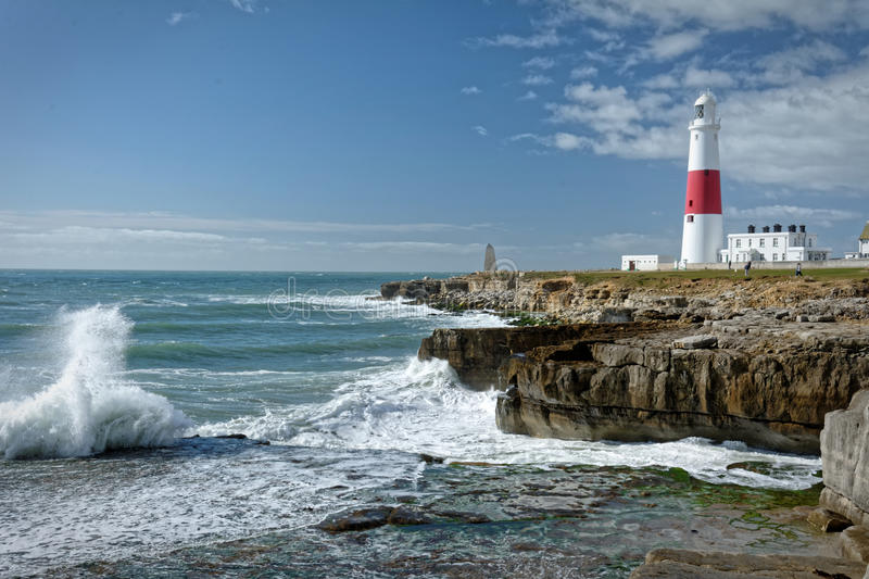 Red and white lighthouse on rocky peninsula. Photo of a tall red and white lighthouse with blue sea crashing against rocks in the foreground. The blue sky stock photos