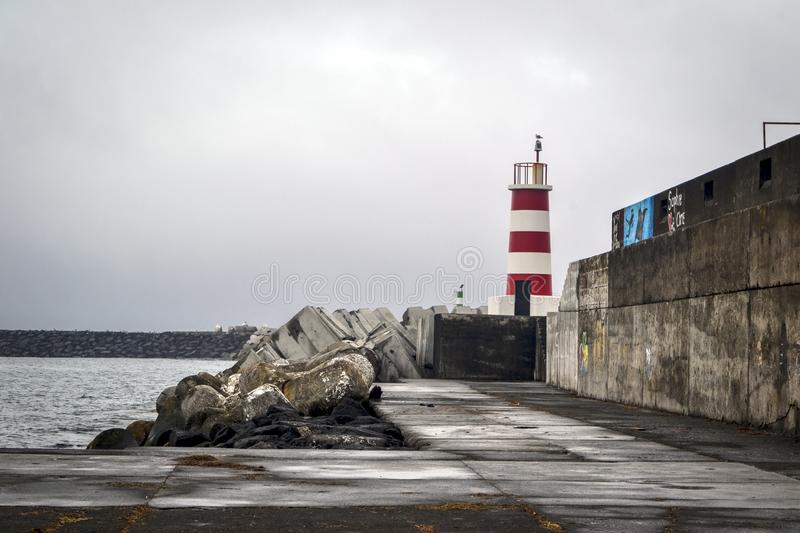 A red white lighthouse on a stone pier in a port on the island of Pico royalty free stock photo