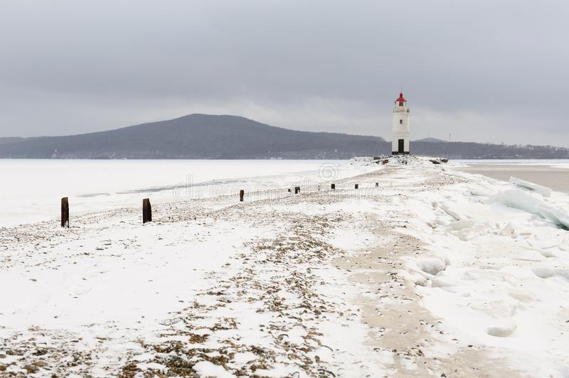 Red and white lighthouse at winter snowy sea coast. stock images