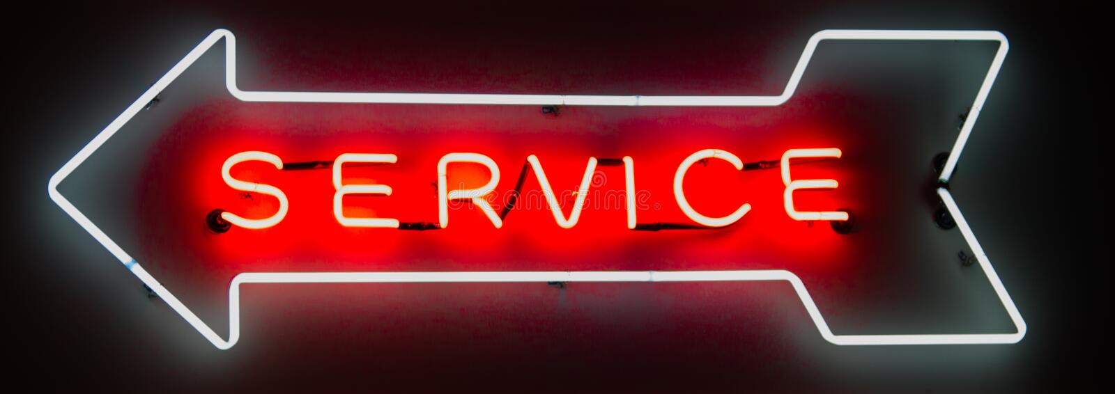 Neon Service Arrow Sign. Red and white neon service sign arrow over black stock photography