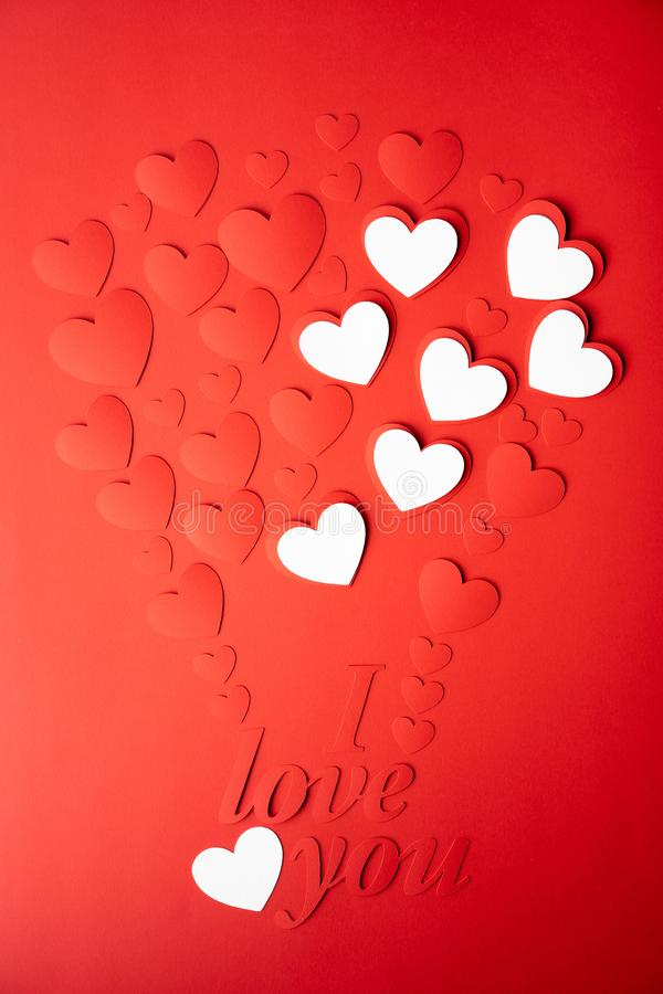 Red and white paper background, cut out hearts are lined up in the shape of a balloon. Words I love you. stock photos