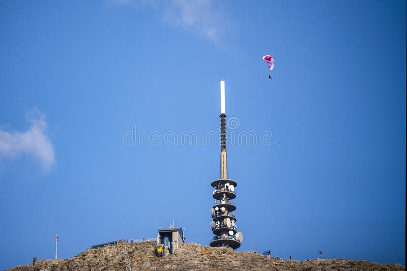 Red and white parag-lider against a blue sky soars over an antenna tower and a gondola. stock images