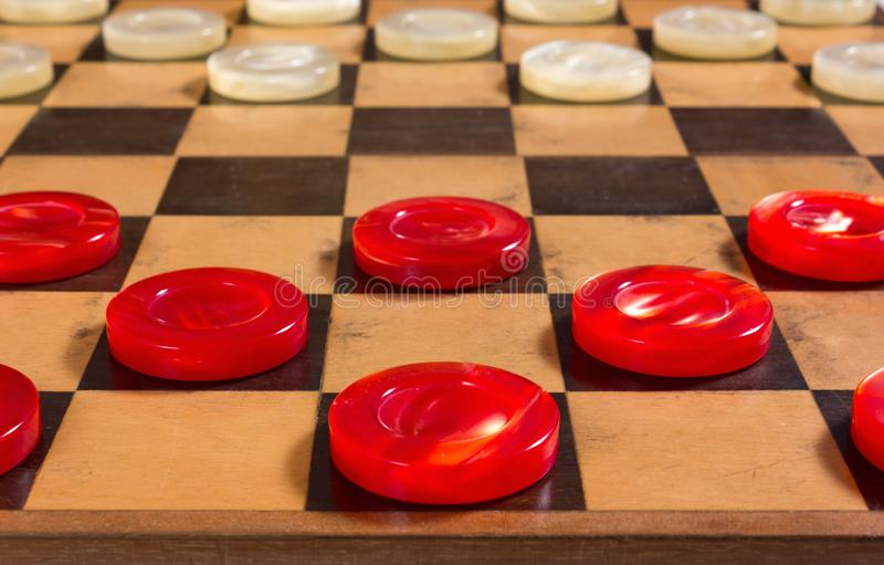 Red and White Pieces on a Checkerboard. Red and white pearly pieces in the starting position on a checkerboard stock images