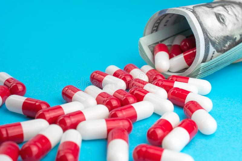 Red white pills spill out of folded dollars. Pharmaceutical industry. red white pills spill out of folded dollars, blue background royalty free stock image