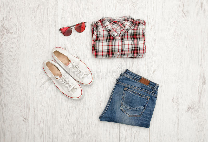 Red and white plaid shirt, glasses, sneakers and jeans. Wooden background. Fashionable concept, top view.  royalty free stock image