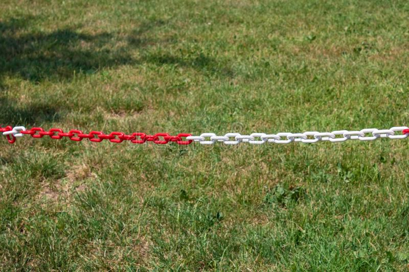 Red and white plastic chain prohibiting parking closeup. Image royalty free stock images