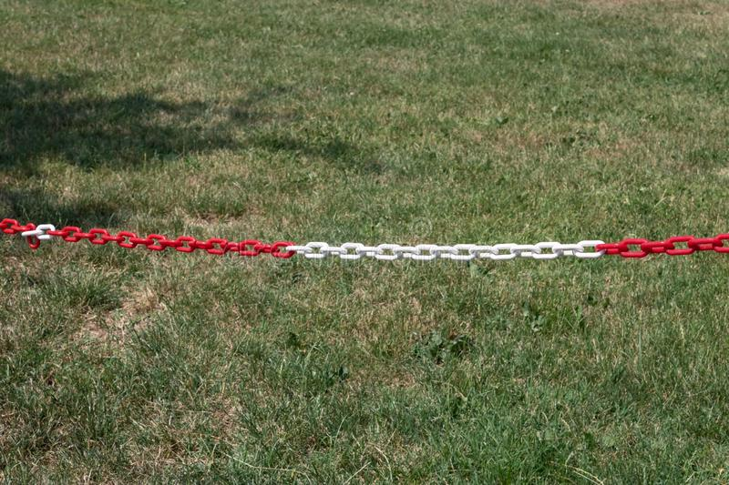 Red and white plastic chain prohibiting passage closeup. Image stock images