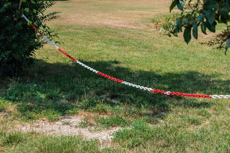 Red and white plastic chain prohibiting passage/parking, hanging on two bushes. Image stock photography