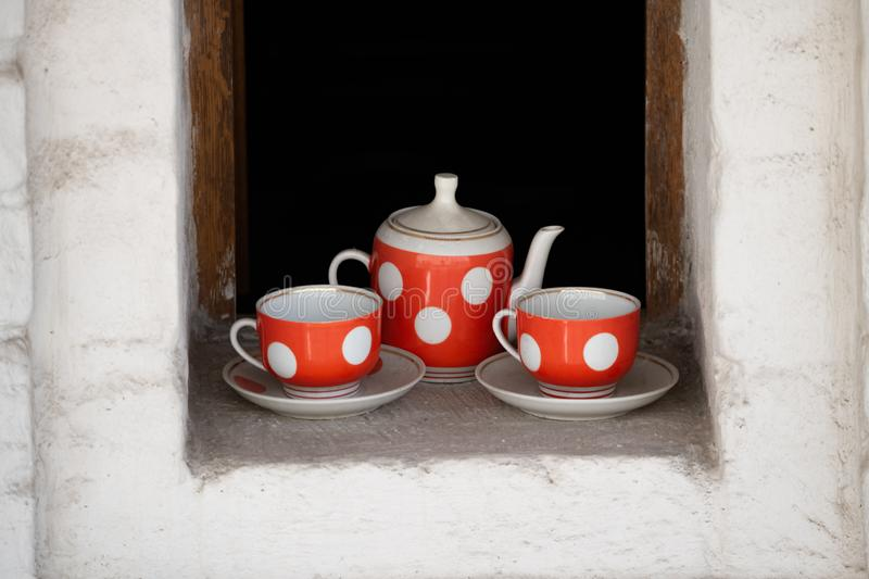 Red white polka dot teapot, cups and saucers. An old tea set stands in the window opening stock images