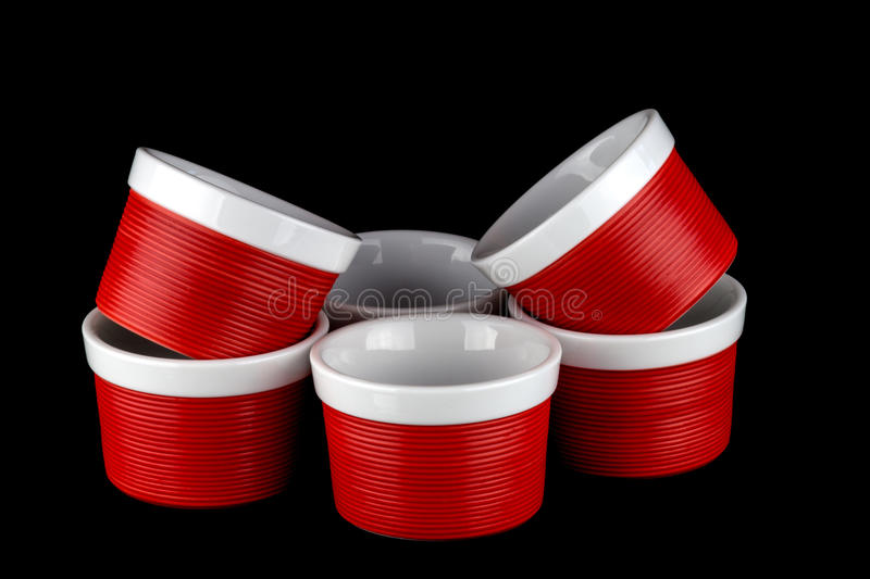 Red and White Ramekins Isolated on Black. Red and white ramekin dishes stacked against a black background stock photo