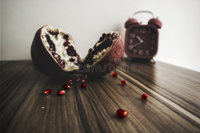 Red and White Round Fruit on Brown Wooden Table With Red Alarm Clock royalty free stock photography