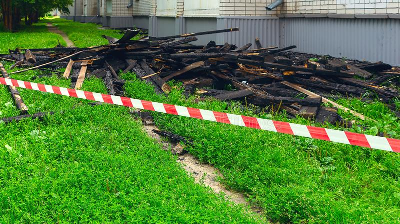 Red and White Safety Tape and Black Charred Rafters, Roof Framework on the Lawn near the Apartment Building after the Fire. Safety stock photo