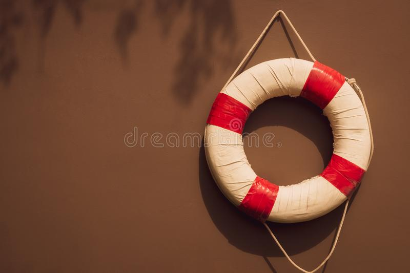 Red and white safety torus or lifebuoy hanging on brown wall stock photography