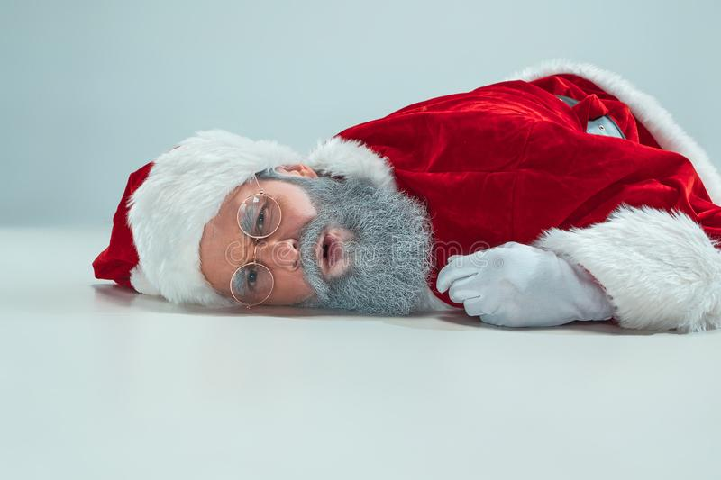 Red white santa claus overworked frustration burnout concept lying on floor isolated on white background royalty free stock photos