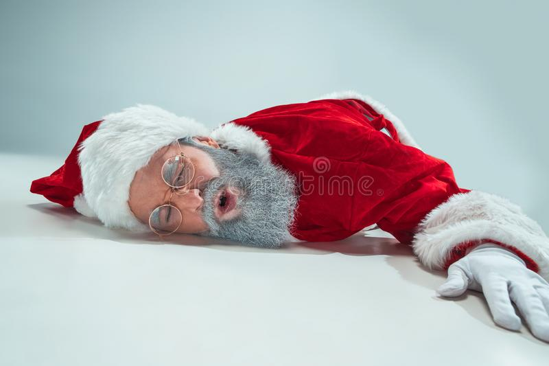 Red white santa claus overworked frustration burnout concept lying on floor isolated on white background stock photo