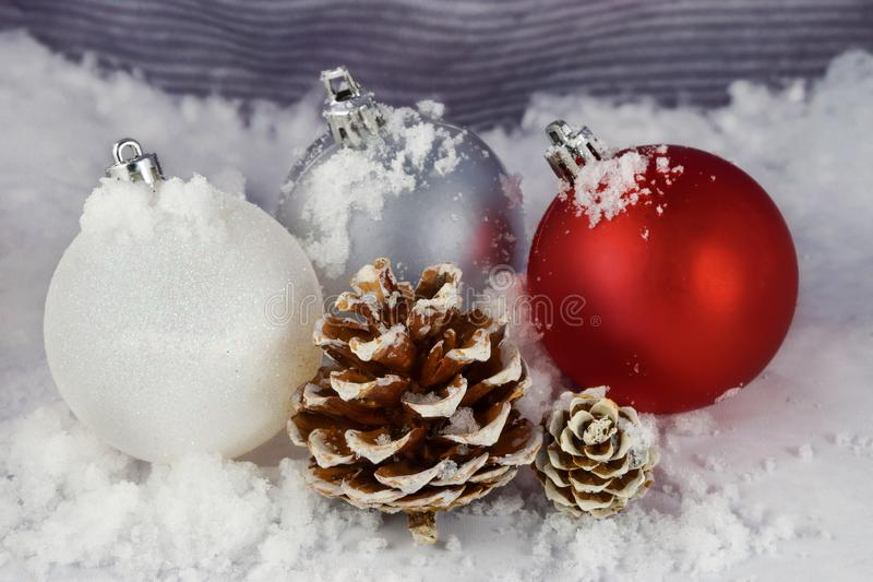 Red White and Silver Christmas Ornaments and a Pinecone on a Snowy Background. stock photography
