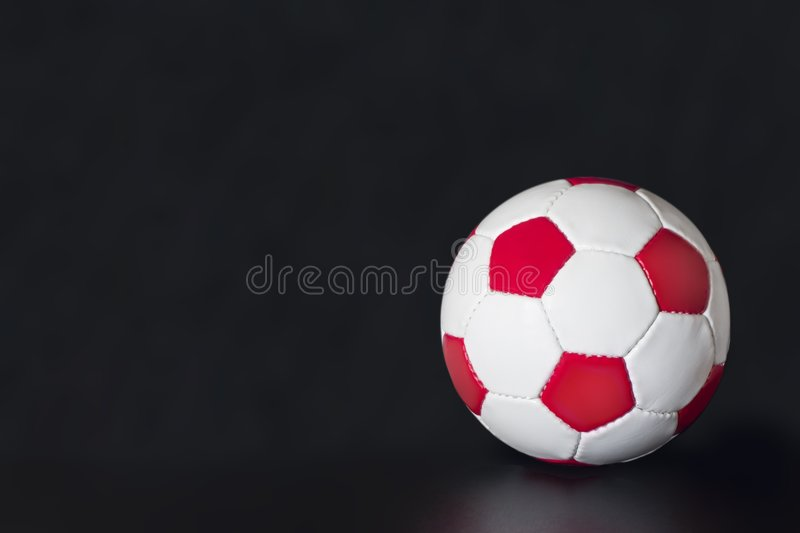Red and white soccer ball on a black background stock photo