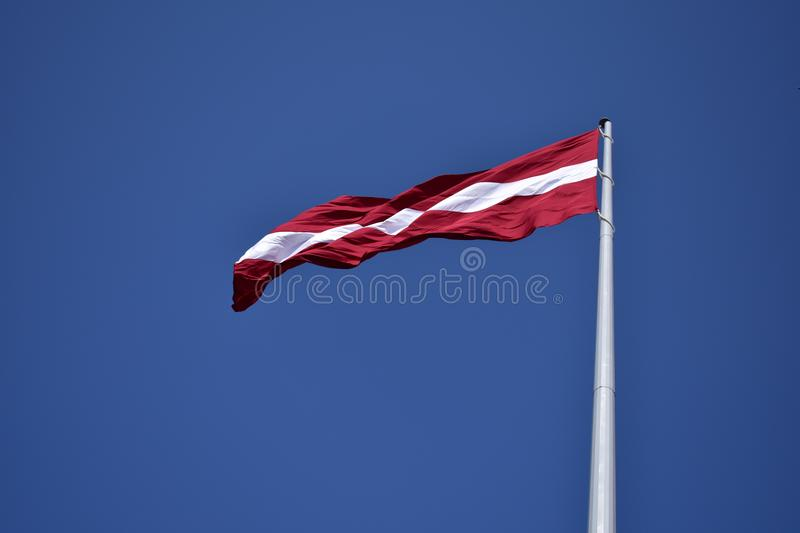 Red and White State Flag Waving Under Blue Sky at Daytime stock image