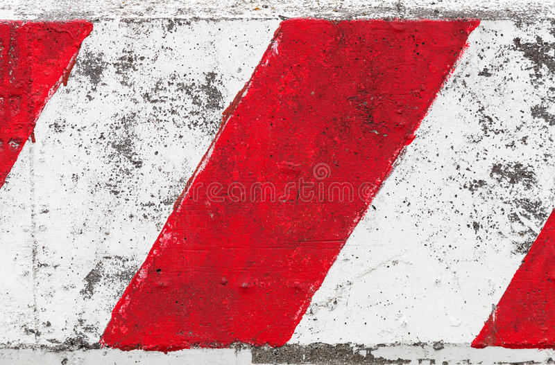 Red and white striped concrete road barrier royalty free stock photography