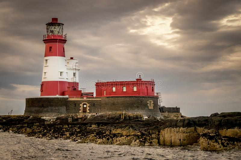 A red and white lighthouse on an island surrounded by storm clouds. A red and white striped lighthouse situated on a rock out at sea at dawn or dusk. unusual royalty free stock photography