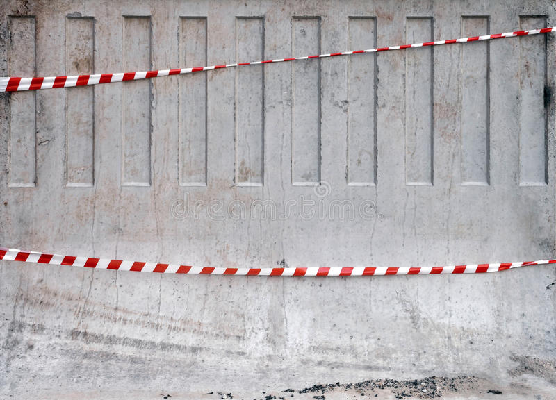 Red and white striped tapes on concrete barrier royalty free stock images
