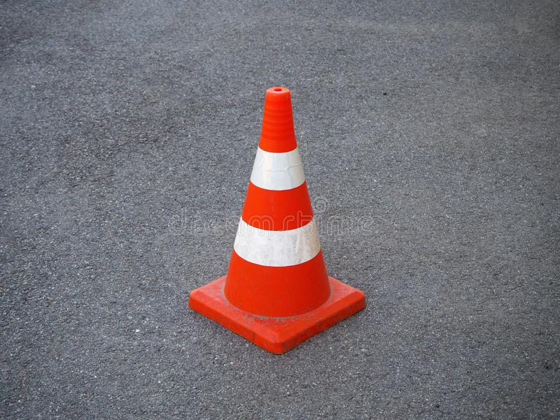 Red and white striped traffic cone on an asphalt road stock photo